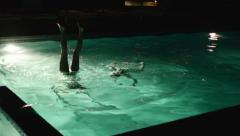 2 Girls Do Handstands Underwater In A Pool At Night Stock Footage