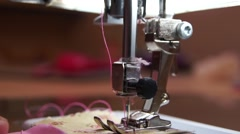 Close up fingers at sewing machine with pink thread, people in the background Stock Footage