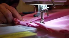 Close up manicured old woman hands sew together pleats of pink fabric Stock Footage