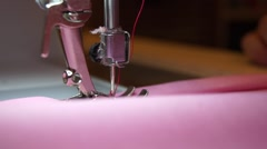 Close up pink fabric being sewn sewing machine foot Stock Footage