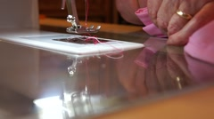 Close up old married womans hands at sewing machine with pink fabric Stock Footage
