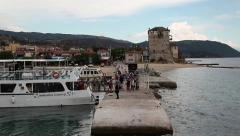 Ship docks to the shore near old tower in Ouranoupoli, Athos peninsula, Greece - stock footage