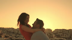 Young couple twirling by marina in sunset. - stock footage