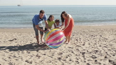 Slow motion shot of family on beach rolling beach ball towards camera. - stock footage