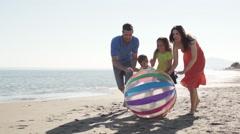 Family chasing beach ball along beach Stock Footage