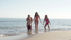 Slow motion of family running out of the sea. Stock Footage