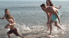 Slow motion of family running along beach at edge of sea. - stock footage