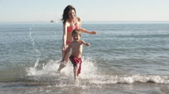 Slow motion mother chasing son out of sea. - stock footage