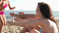 Slow motion family on beach, children running to parents. - stock footage