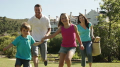 Slow motion of family running to camera in a park. - stock footage
