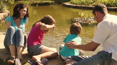 Dolly shot of family in park fishing with nets in lake. - stock footage