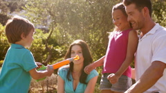 Slow motion of family playing with bubbles in park - stock footage