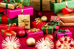 numerous xmas gifts arranged on a red cloth. - stock photo
