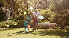 Slow motion of family in park running with balloons. Stock Footage