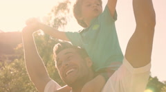 Father with son on shoulders in park. - stock footage