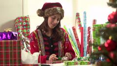 Woman wrapping Christmas present in holiday sweater - stock footage