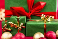 four xmas presents with bows in gold and red. - stock photo
