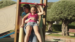 Slow motion of mother and daughter on slide in park Stock Footage