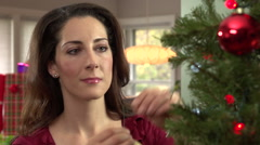 Woman decorating Christmas tree, close up Stock Footage