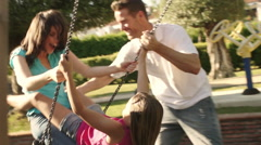 Slow motion of family in park father pushing mother and daughter on swing. - stock footage