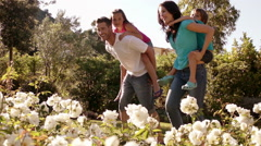 Slow motion of family running in park, parents carrying children on backs. Stock Footage