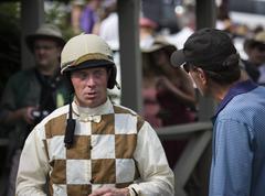 Experienced jockey talks to a horse owner Stock Photos