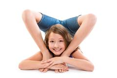 Flexible contortionist kid girl playing on white Stock Photos
