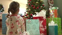 Little girl sitting in front of Christmas tree - stock footage