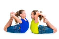 Stock Photo of twin kid sisters symmetrical flexible playing happy