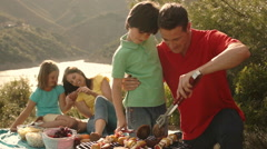 Dolly shot of family having barbecue picnic by lake in countryside. - stock footage