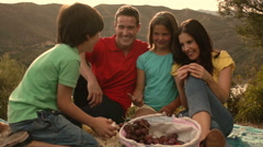 Slow motion family having picnic by lake in countryside. - stock footage