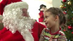 Little girl on Santa's lap asking for Christmas gift - stock footage