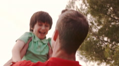 Father holding up son overlooking lake in countryside. - stock footage
