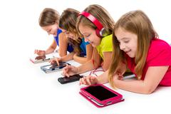 Stock Photo of sisters kid girls tech tablets and smatphones