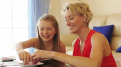 Dolly shot of grandmother and granddaughter decorating cup cakes indoors. - stock footage