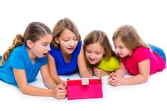 Stock Photo of sisters kid girls with tech tablet pc playing happy