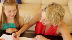 Dolly shot of grandmother and granddaughter drawing together indoors. - stock footage