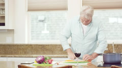 A man is busy chopping food when he gets a phone call and stops to answer it Stock Footage