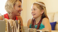 Grandmother and granddaughter playing with jewellery together indoors. - stock footage