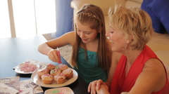 Dolly shot of grandmother and granddaughter making cup cakes together indoors. Stock Footage