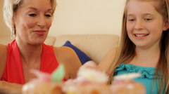 Grandmother and granddaughter eating cup cakes together indoors. - stock footage