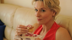 Dolly shot of single woman eating cup cake indoors - stock footage