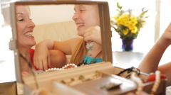 Grandmother and granddaughter playing with jewellery together indoors. Stock Footage