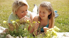 Dolly shot of grandmother and granddaughter playing with flowers in park. - stock footage