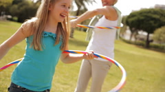 Grandmother and granddaughter playing with hula hoops in park. - stock footage