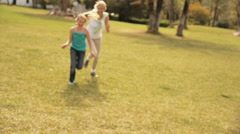 Grandmother and granddaughter running and hugging in park. - stock footage