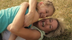 Grandmother and granddaughter hugging in park. - stock footage