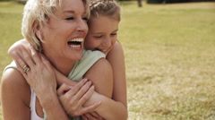 Grandmother and granddaughter hugging in park. Stock Footage