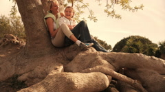Dolly shot of grandmother and granddaughter sitting on tree root in park. - stock footage