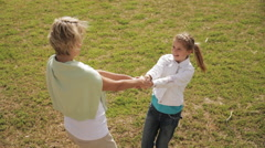 Grandmother and granddaughter twirling around in park. - stock footage